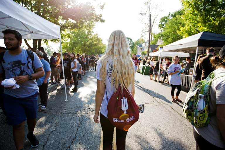 a woman with an Indiana University backpack at an outdoor street fair
