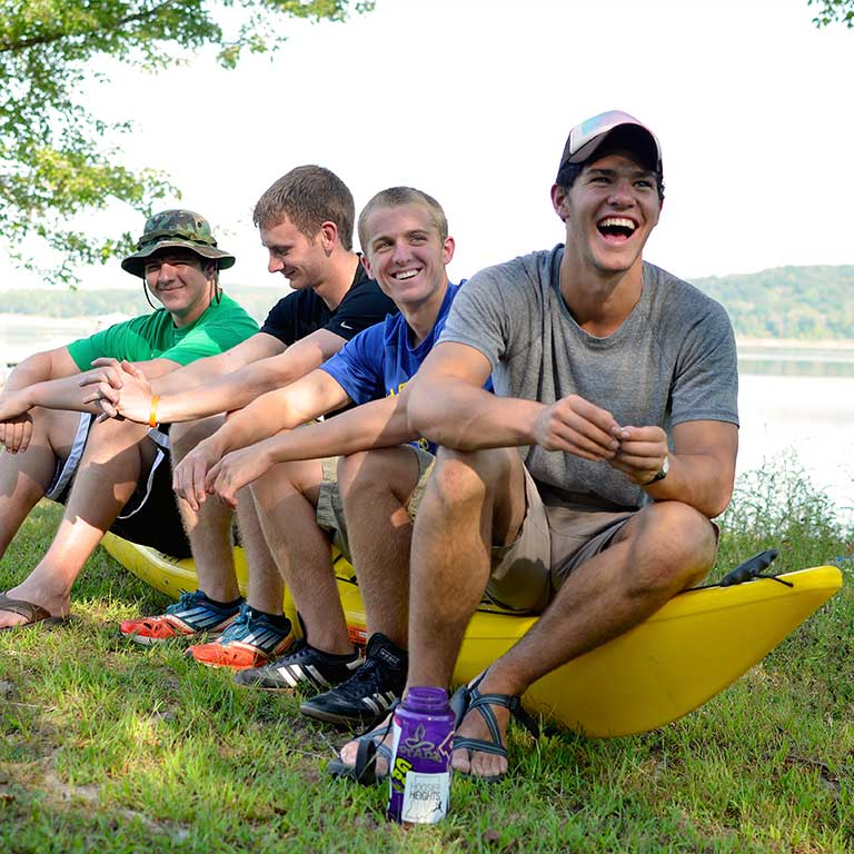 four young men sitting on a kayak
