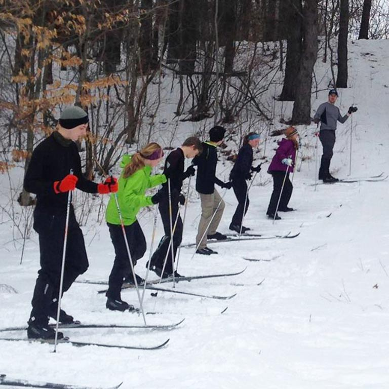 several young people and an instructor wearing cross country skis