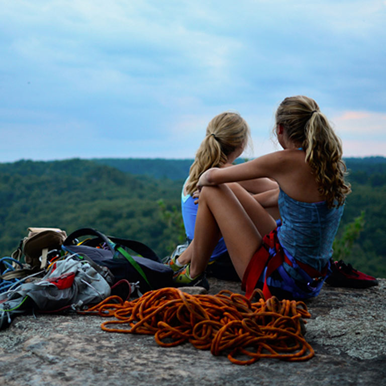 two rock climbers sitting next to a pile of climbing rope