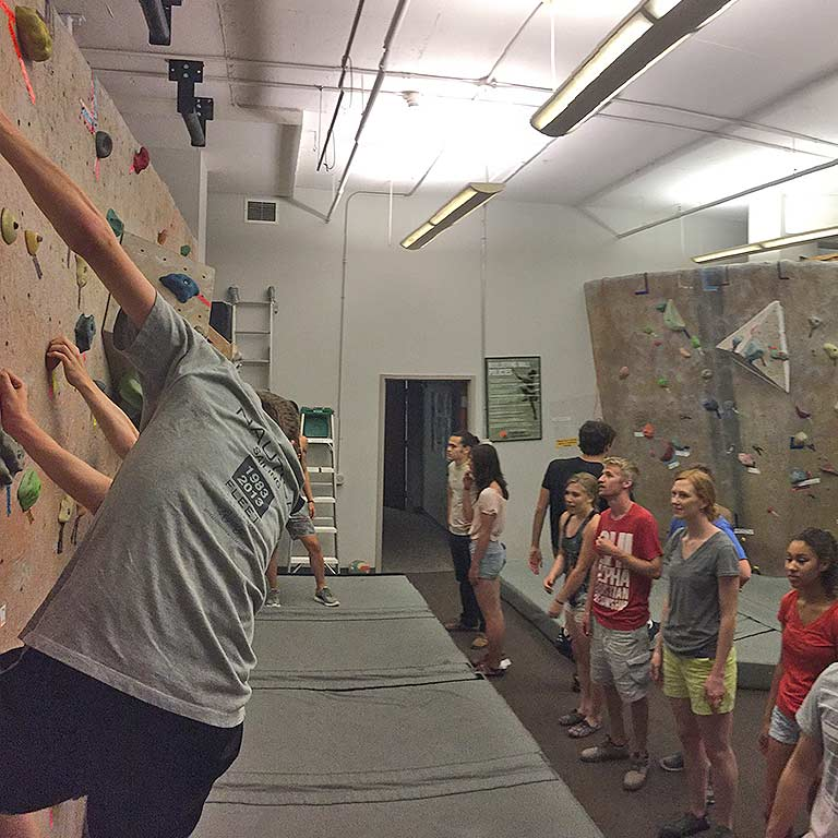 students watch other students practice indoor rock climbing