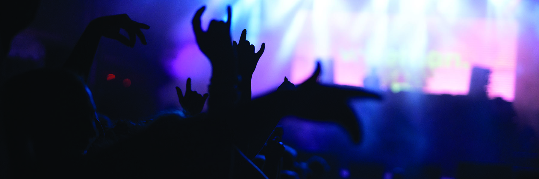 silhouetted hands raised at a concert