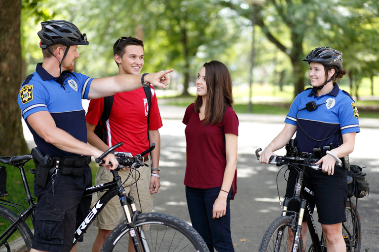 two students talking to two police officers who are on bicycles