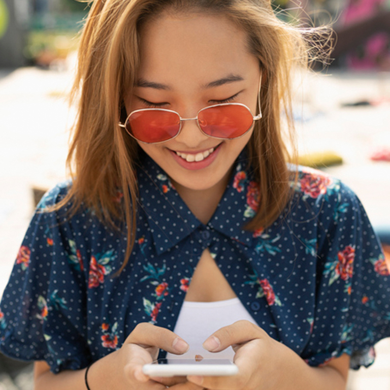 a woman wearing rose colored sunglasses, texting on smartphone