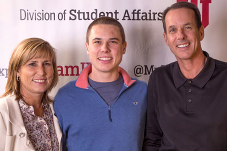 a mom dad and students smiling in front of a backdrop that says division of student affairs