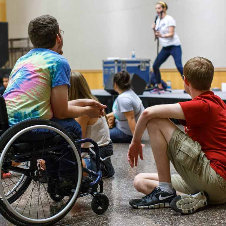 a woman performs on stage in a front of a group that includes a young man in a wheelchair, wearing a tie-dye shirt