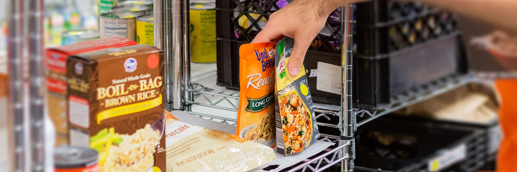 a hand placing packets of rice on a metal storage shelf