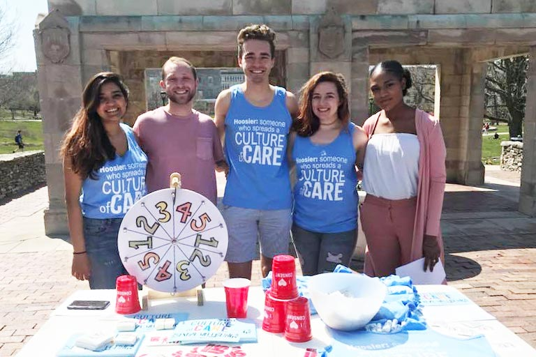 students wearing shirts that say culture of care, standing behind a table with papers and a game wheel on it