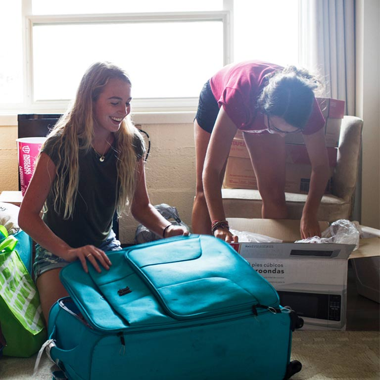 two young women in a room. One is opening a blue suitcase, the other is opening a box.