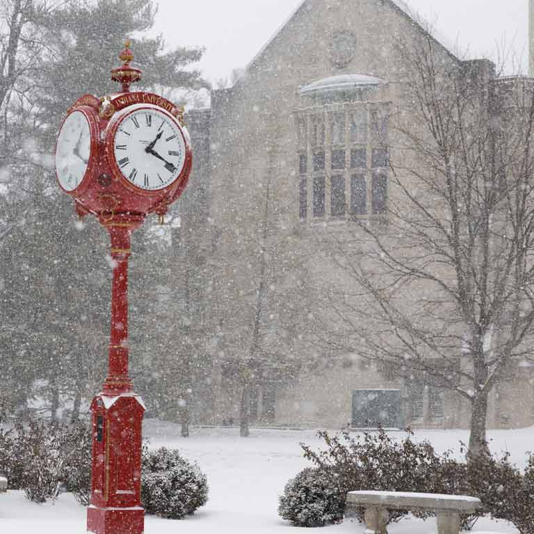 a tall red clock on the IU campus on a snowy day